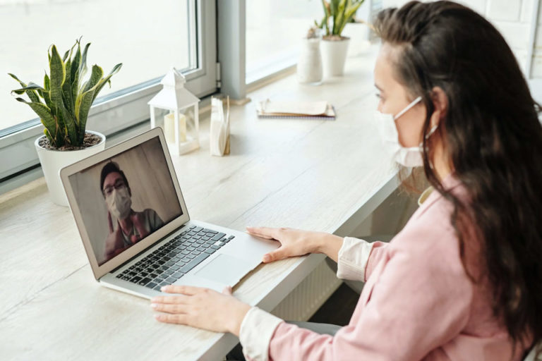 A woman on a laptop during a telemedicine visit